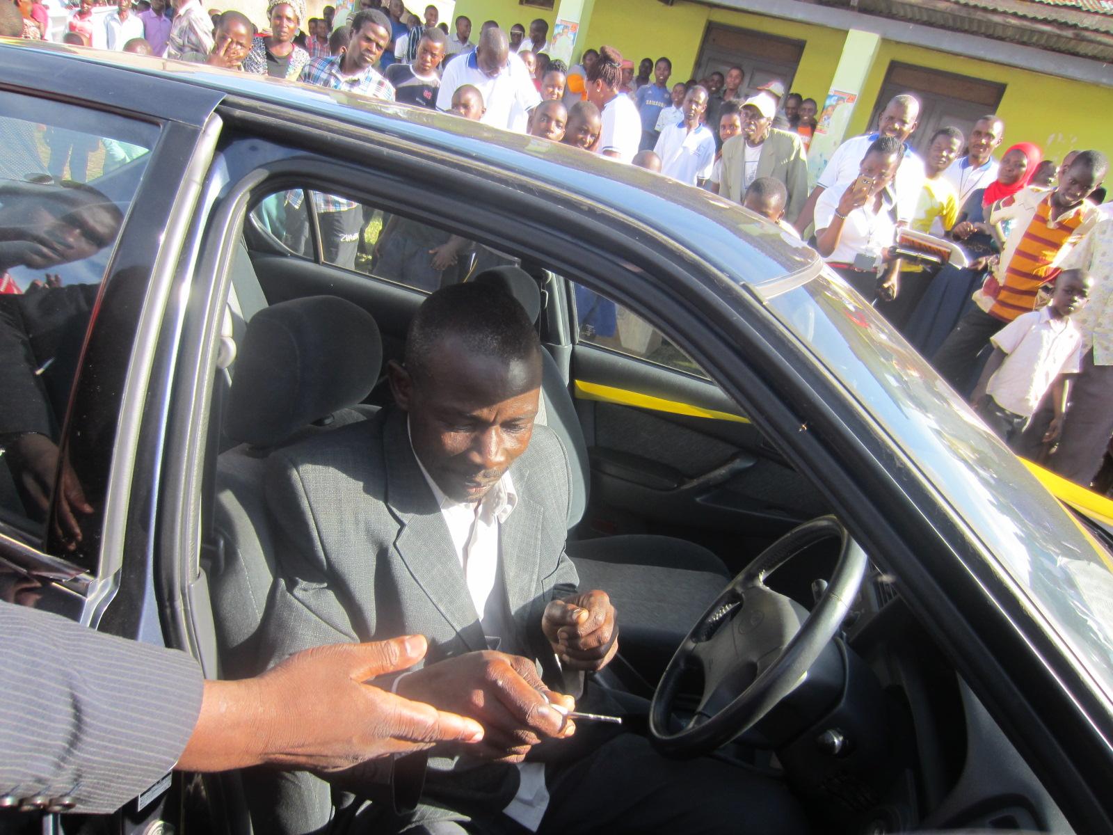 Mr.Ssebyara starting the vehicle and thereafter Bishop Katoneene prayed for the winner.