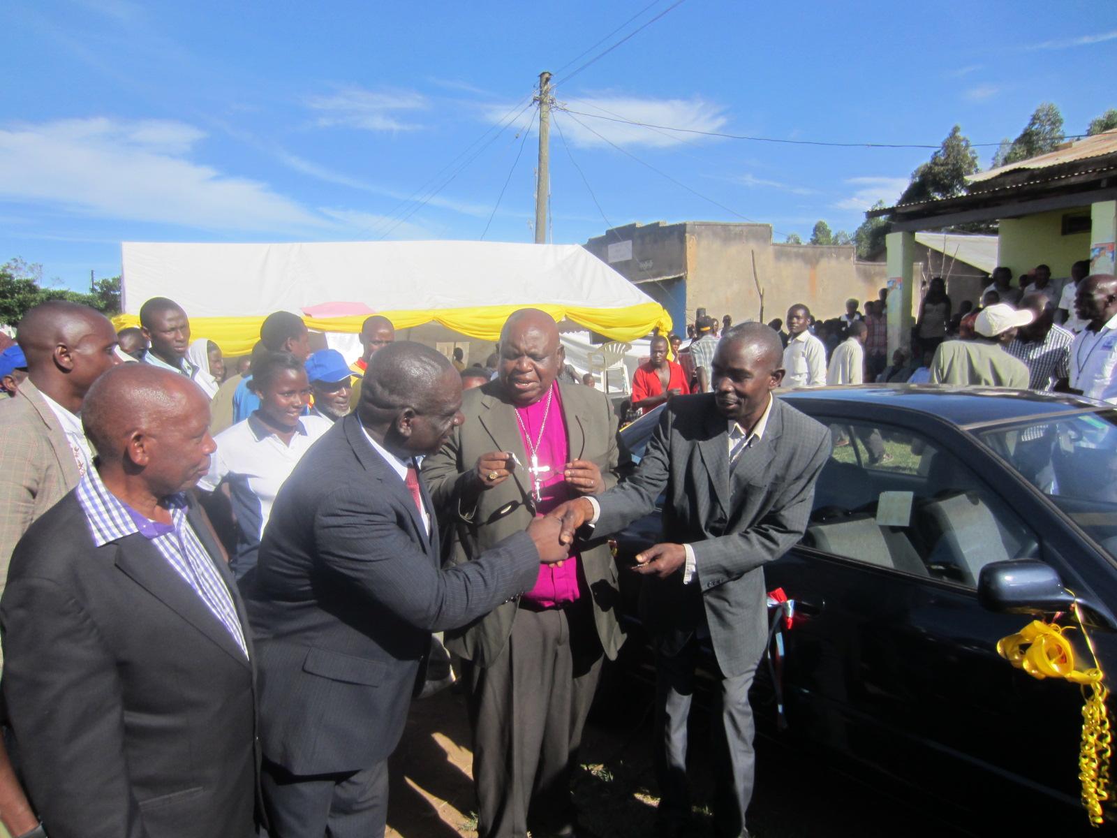 The winner of the car, Mr. Abubak Ssebyara receiving keys from RTD Bishop Katoneene